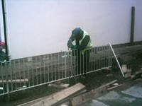 Blacksmith welding steel railings in place -  Camlachie Phase 5 Glasgow
